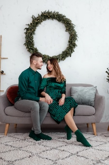 Loving happy couple at home. family, christmas, holidays, love and people concept - happy young pregnant couple sitting hugging on sofa at home near christmas tree. selective focus.