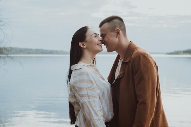 抱きしめて笑っている愛する幸せなカップル。夏の川沿いのボーイフレンドとガールフレンド