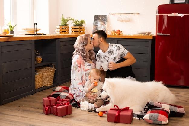 クリスマスの時期に自宅のキッチンで一緒に時間を楽しんでサモエド犬と一緒に幸せな家族を愛する