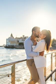 Влюбленная пара испаноязычных обнимается на набережной
