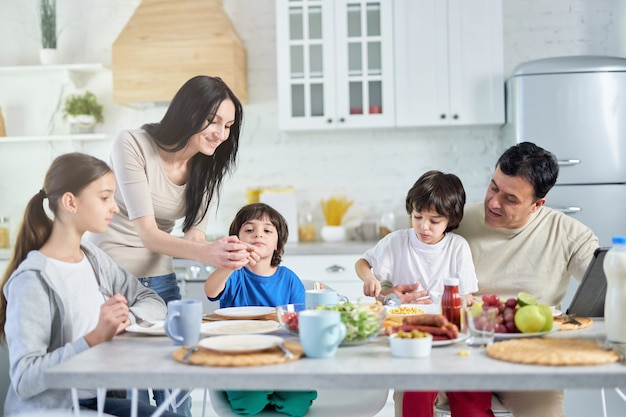 사랑하는 히스패닉계 부모가 어린 자녀를 돌보고 집에서 함께 점심을 먹으면서 그들을 즐겁게 합니다. 어린 시절, 부모, 라틴 요리 개념