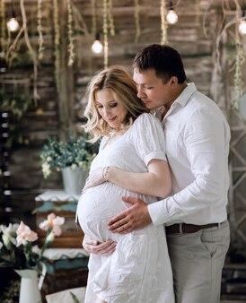 사랑하는 남편이 임신 한 아내를 부드럽게 껴안고 있습니다. 아기의 탄생을 기대하는 행복한 가족.