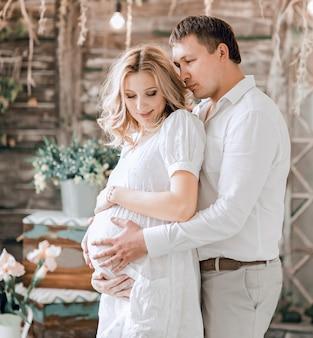 사랑하는 남편이 임신 한 아내를 부드럽게 포옹합니다. 아기의 탄생을 기대하는 행복한 가족.