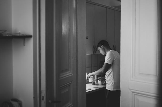 사랑하는 남편이 아내를 위해 부엌에서 커피를 준비하고 있습니다.