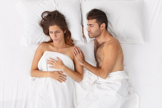 愛する夫は、問題を抱えている妻を支えて落ち着かせ、白い寝具の下で一緒にベッドにとどまり、否定的な感情を表現しようとします。家族の悩み、人間関係、ストレスの多い状況