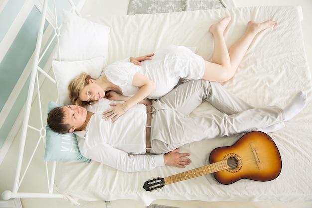기타와 함께 사랑하는 남편과 침대에 임신 한 아내