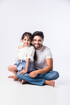Loving indian daddy embracing cute little adorable daughter sitting over lap or piggyback - concept showing love, care, closest person, fathers day