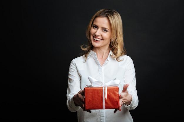 Любящая добрая молодая женщина выражает позитив и демонстрирует подарочную коробку, стоя у черной стены