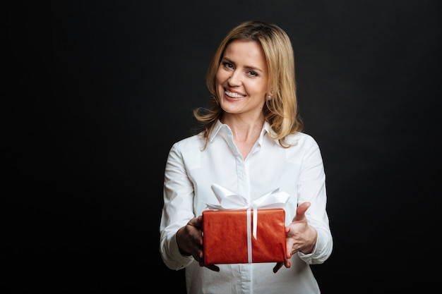 Loving kind young woman expressing positivity and demonstrating gift box while standing against black wall