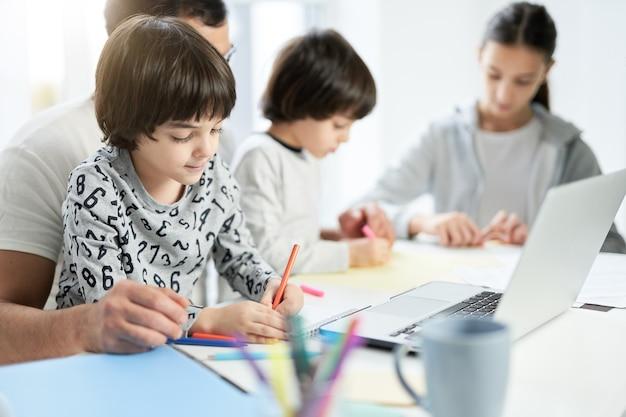 그의 아이와 노는 사랑 라틴 아버지. 사업가는 그의 아들이 노트북을 사용하고 집에서 일하고 아이들을 보면서 그림을 그리는 것을 돕습니다. 프리랜서, 잠금, 가족 개념