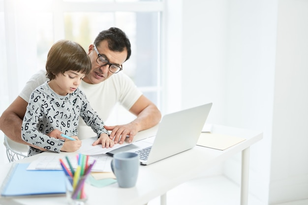 Loving latin father playing with his son. businessman using laptop while working from home and watching child. freelance, lockdown, family concept