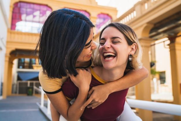 Loving lesbian couple having fun at the street.