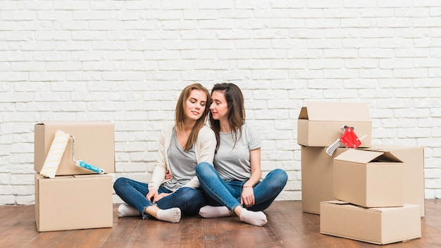 Loving lesbian young couple sitting on hardwood floor with moving cardboard boxes in their new house