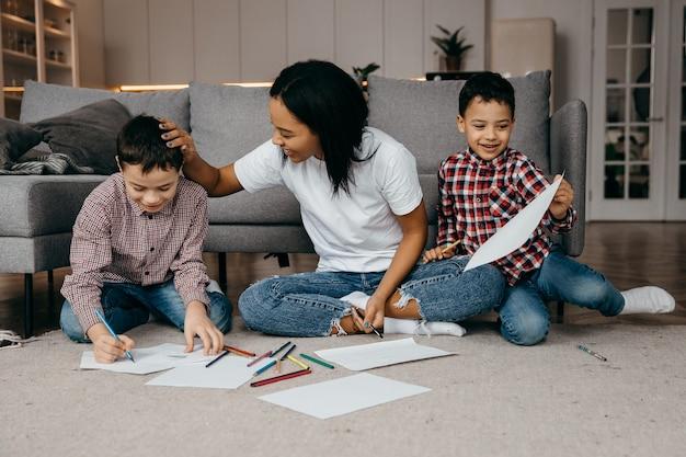 사랑하는 어린 소년들이 엄마를 위해 그림을 그리고 엄마가 행복하고 기뻐한다는 것을 보여줍니다.