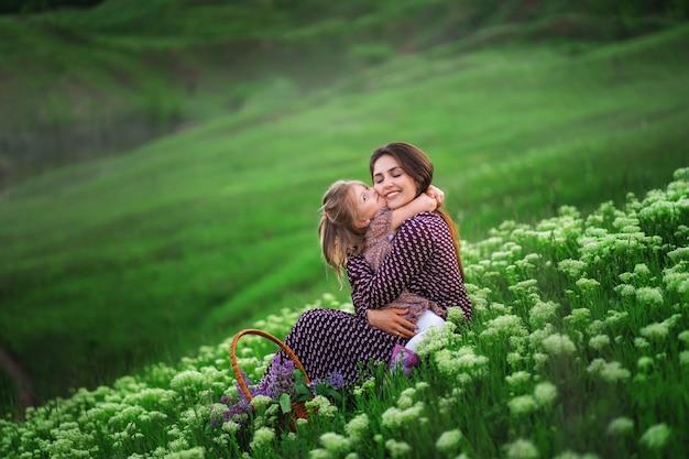 幸せなお母さんを抱き締め、母の日に挨拶する愛情のある小さな娘