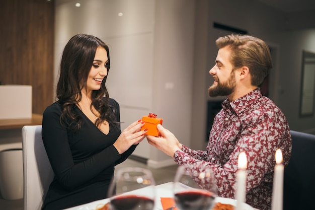 Loving man giving small gift to girl