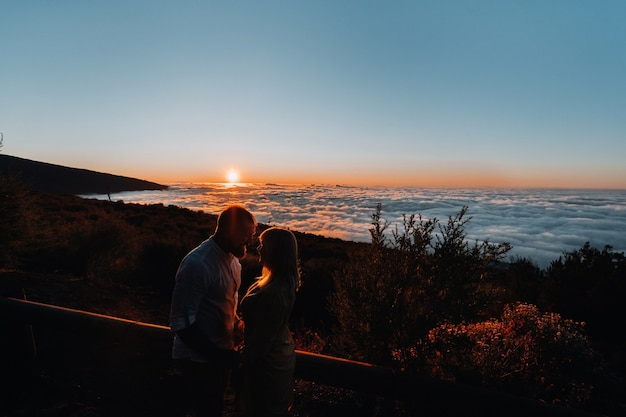 A loving man holds the girl s hand at sunset, on the background of the sea, portrait of handsome newlyweds. photograph, concept.