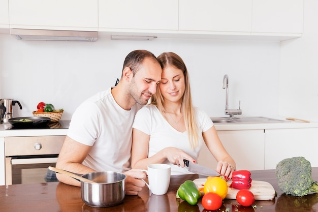 Loving man sitting with his wife cutting the vegetables with knife