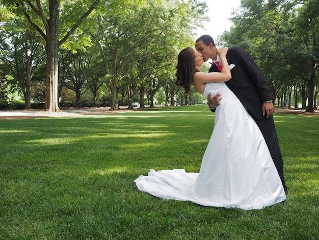 木の完全な緑豊かな公園でキスする夫婦を愛する