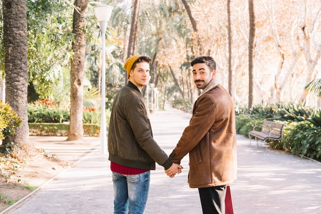 Loving men holding hands posing in park