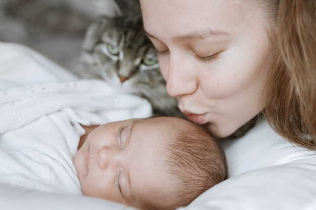 Loving mom carying of her newborn baby at home baby is resting in bed