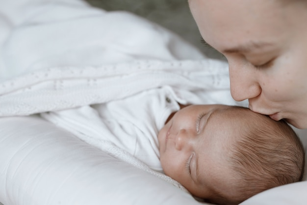 Loving mom carying of her newborn baby at home
