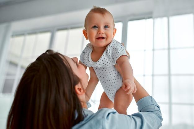 自宅で生まれたばかりの赤ちゃんを世話する愛情のあるお母さん。日当たりの良い寝室で遊ぶお母さんと男の子。親と小さな子供が家でリラックス。一緒に楽しんでいる家族。育児、出産の概念。
