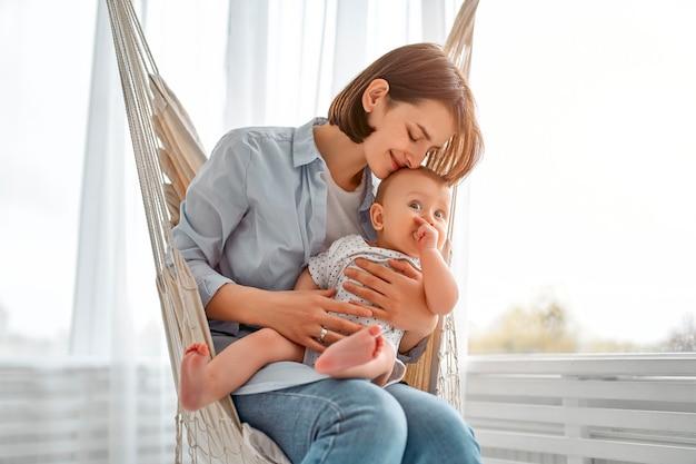 집에서 신생아를 돌보는 사랑하는 엄마. 메쉬 해먹에 엄마와 아이. 맑은 침실에서 노는 엄마와 아기 소년. 부모와 작은 아이가 집에서 휴식. 가족이 함께 재미.