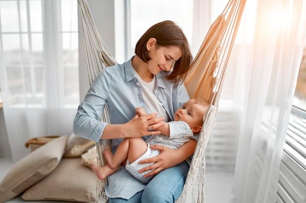 Любящая мама ухаживает за своим новорожденным ребенком дома. мать и ребенок на сетчатом гамаке. мама и мальчик, играя в солнечной спальне. родитель и маленький ребенок отдыхают дома. семья весело вместе.