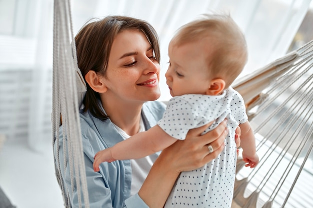 家で生まれたばかりの赤ちゃんを世話する愛情深いお母さん。メッシュハンモックで母と子。日当たりの良い寝室で遊ぶママと男の子。親と小さな子供が家でリラックス。一緒に楽しんでいる家族。