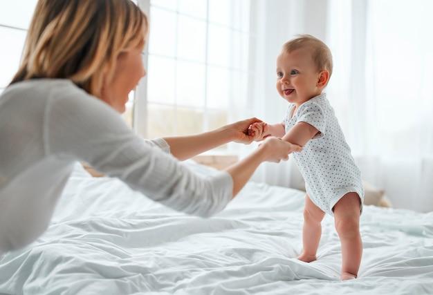 Любящая мама ухаживает за своим новорожденным ребенком дома. мать и ребенок на белой кровати. мама и мальчик в подгузнике, играя в солнечной спальне. родитель и маленький ребенок отдыхают дома. семья весело вместе.