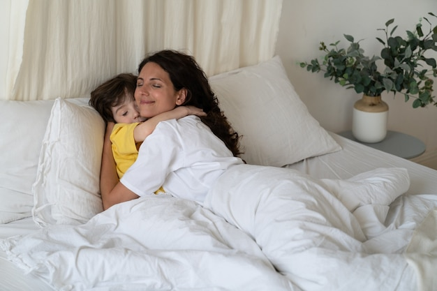愛情深いお母さんはベッドに横たわっている小さな子供の男の子を抱きしめます幸せな母親は子供と一日を過ごすために家にいます