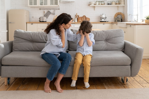 Loving mom try to comfort son offended or abused in kindergarten little preschool boy cry on sofa