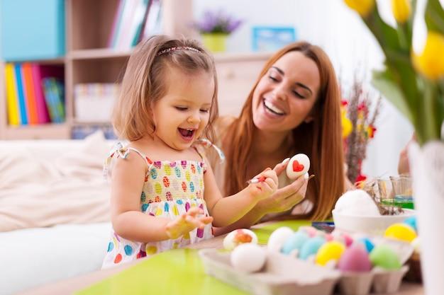 愛情深い母親と赤ちゃんがイースターエッグを描く
