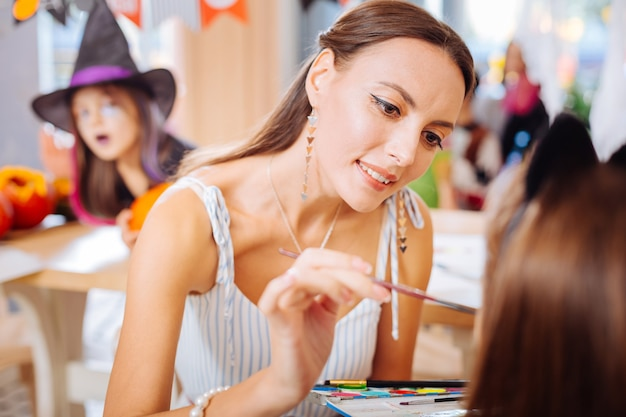 Loving mother. caring loving mother feeling attentive while painting face of her little daughter for halloween party