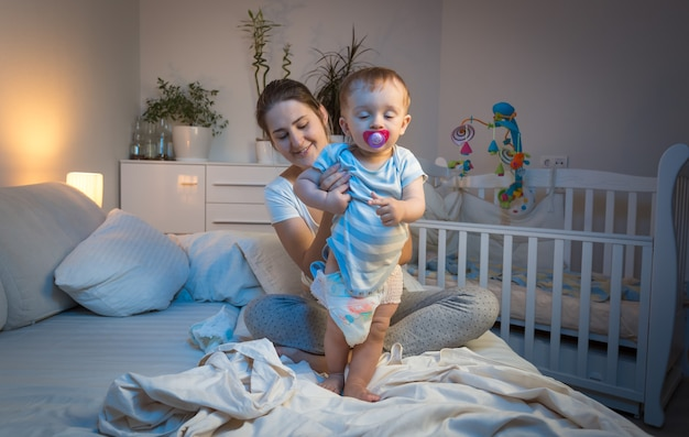 Loving mother changing diapers to her baby son on bed
