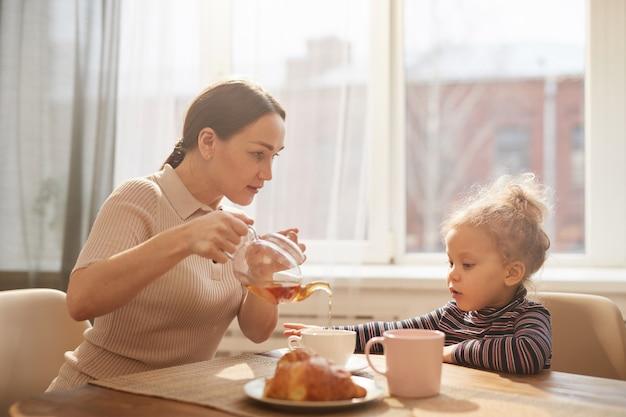 かわいい小さな娘と一緒に朝食を楽しんでいる愛情深い母親