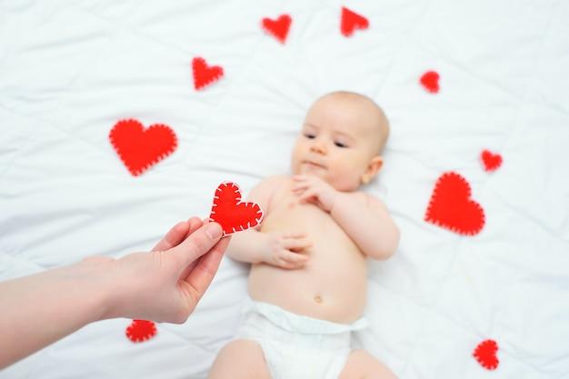 Любящая мать дарит сердечко-валентинку своему маленькому сыну, который лежит на множестве сердечек