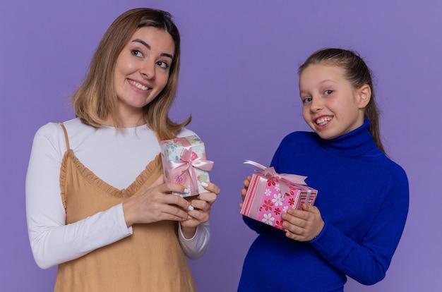 Madre amorevole e figlia felice che tengono i regali