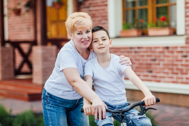 Loving mother help her cute grandson ride a bicycle near garden. family photo.