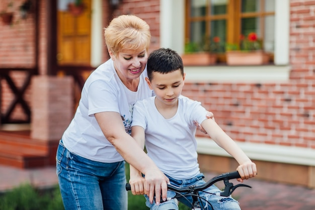 Loving mother help her cute grandson ride a bicycle near garden. how to ride a bike..