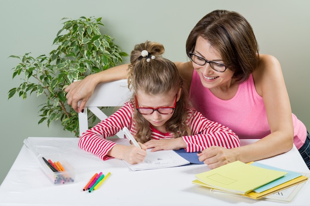 Loving mother helping her daughter elementary school pupil write