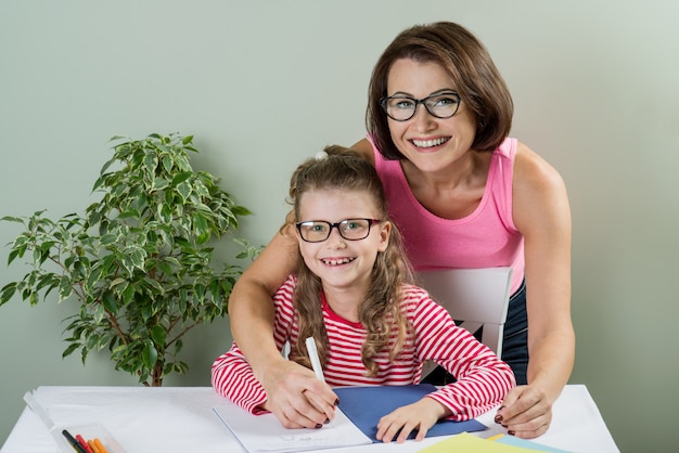 Loving mother helping her daughter write in her notebook