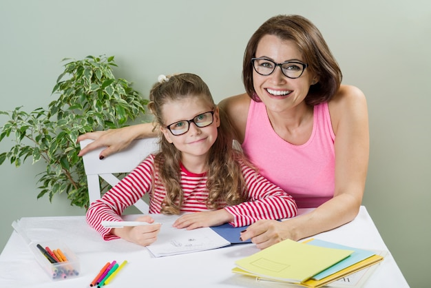 Loving mother helping her daughter write in notebook
