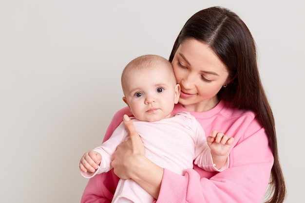 愛情深い母親が赤ちゃんを手に持って抱きしめ、黒い髪の女性がカジュアルなピンクのセーターを着て娘を見て、白い壁に孤立してポーズをとっています。