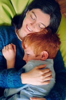 Loving mother hugging her son being playful. childhood concept. single woman playing with his child at home. family lifestyle inside the house with children. entertainment for little kids indoors.