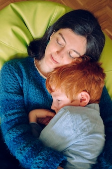 Loving mother hugging her son with nightmares trying to make him sleep. insomnia and sleeplessness concept. single woman with his child at home. family lifestyle inside the house with children.