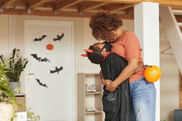 Loving mother kissing her cute son wearing devil costume with red horns before letting him go out for trick or treating with other kids
