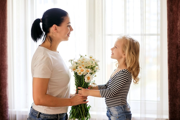 Loving mother and little daughter at home with a bouquet of daisies. the family is having a good time together.