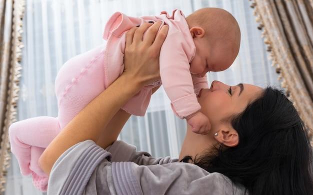 彼女の小さな女の赤ちゃんと遊んでいる愛情深い母親は、クローズアップの優しい屋内肖像画で彼女を高く持ち上げます